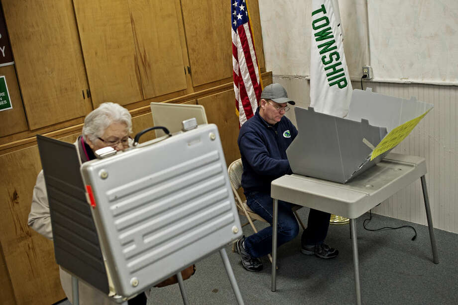Scott Elmore, of Hope, fills out his ballot on Tuesday at Hope Township Hall. Election officials said that voter turnout has been strong throughout the day. Photo: SEAN PROCTOR | Sproctor@mdn.net
