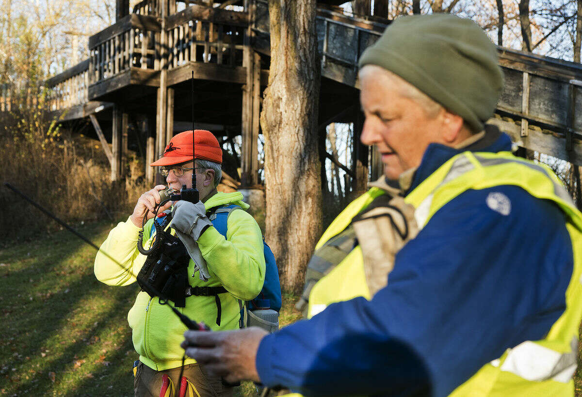 Dave Wallick, of Midland, left, and Wendy Gilbert, of Saginaw, check their radios during the Midland County Search and Rescue training session at Midland City Forest on Saturday. Wallick said he has been volunteering with the group for about a year; Gilbert has been a member for two years.