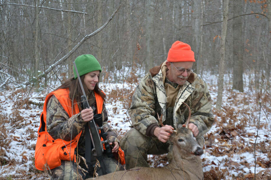 Ken Haustein of Midland and his daughter Corie Oberson of Auburn admire the three-point buck Haustein shot as the pair hunted together in Midland County last year. Photo: Steve Griffin | For The Daily News