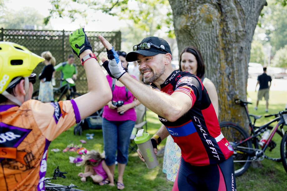Roy Kranz high fives his son, Kahler, 11, at the Sweat Shaker race at Mid Michigan Community College on June 28. Kahler competed in the youth division while Kranz came in first place in the Sport category. Photo: NEIL BLAKE | Nblake@mdn.net