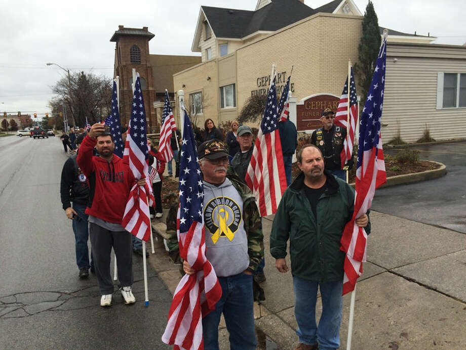 People with flags are shown today along Midland Street in Bay City in front of Gephart Funeral Home. Photo: Nick King | Nking@mdn.net