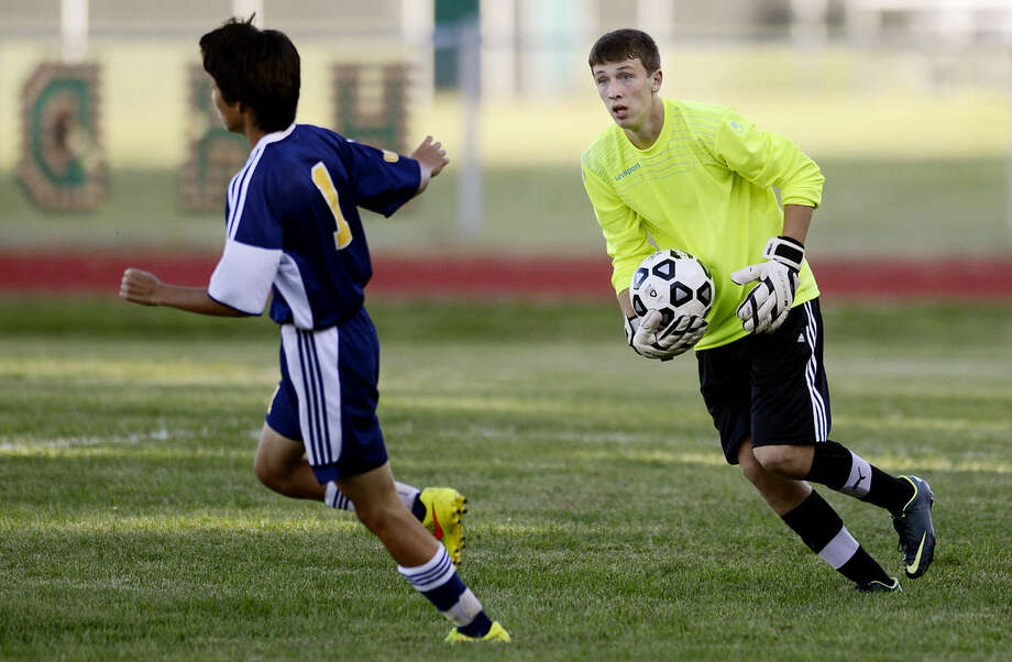 Dow goalie Josh Storer, right, picks up the ball before Mount Pleasant's Michael Shin can get to it during the second half Monday at Dow High School. The game ended in a 1-1 draw. Photo: NICK KING | Nking@mdn.net