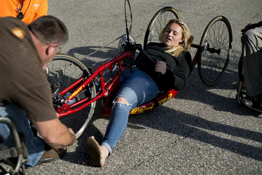 Brooke Back, 18, of Midland, gets situated on a handcycle during at Emerson Park in Midland on Thursday during a hand cycling clinic put on by Special Tree Midland Neuro Skills Center. The event served to educate attendees about the cycles and the benefits for cycling. The hand cycles are especially useful to paraplegics but can be used by anyone. Back is a longtime volunteer at Special Tree. Fusion Medical Supplies supplied most of the handcycles for people to try. Photo: Neil Blake/Midland Daily News