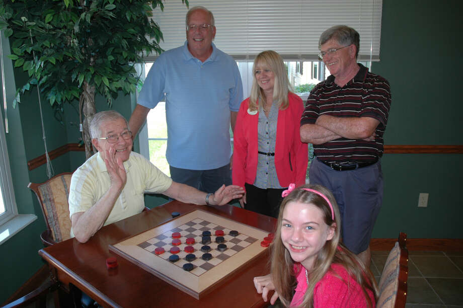 Jerry Geyer, a resident of Bickford Cottage, plays checkers with Taylor Murdick at the senior living facility. Standing, from left, are Paul Fritz, past president of Midland Woodworker's Association; Kelly Kubesh, life enrichment coordinator at Bickford Cottage; and Don Taylor, president of MWA. Photo: Photo Provided