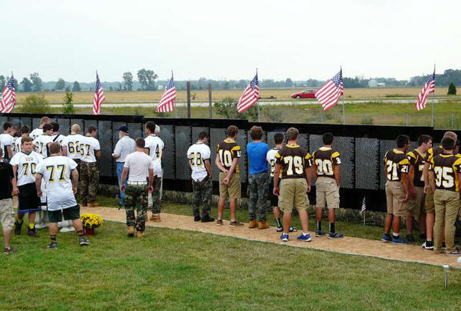Dow High and Bay City Western football players visit the Moving Vietnam Wall in Auburn City Park on Friday evening before their football game. Photo: JON BECKER | For The Daily News
