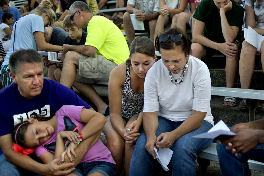"""The Lloyd family, from left, Chuck, Grace, 10, Annie, 18, and Nicole, pray with others during a back-to-school prayer service on Monday at Midland Community Stadium. The interdenominational service was held for students, teachers, parents, administrators, coaches and support staff. """"It's good that all the churches can come together for something like this,"""" Chuck said. Photo: NICK KING 