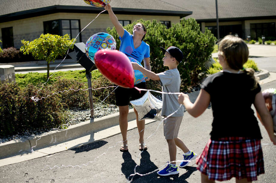 """Josyln Coppens releases balloons with her children, Easton Krenzke, 9, and Taylor Krenzke, 11, to mark the birthday of her late husband, Jason Krenzke, who died in 2012 at the age of 33 after a nearly five-year battle with brain cancer. """"Happy birthday!"""" they said as they released the balloons, """"We love you."""" Coppens is a board member for the Children's Grief Center, a new nonprofit organization in Midland to help children and teens who have experienced the death of a parent, sibling, close family member or friend. Photo: NEIL BLAKE 
