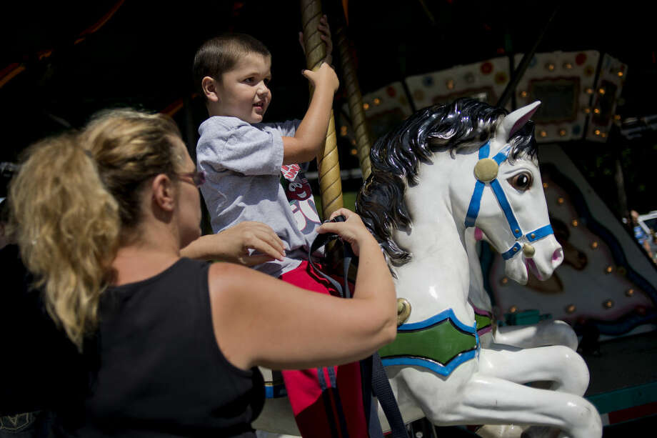 NICK KING | nking@mdn.net Jennifer Hunter, left, helps her son Gavin, 4, onto a horse before a carousel ride during Founders Day on Saturday at the Sanford Centennial Museum. The event was presented by the Sanford Historical Society. Festivities continue on Sunday from 8 a.m. to 4 p.m. Photo: Nick King/Midland  Daily News