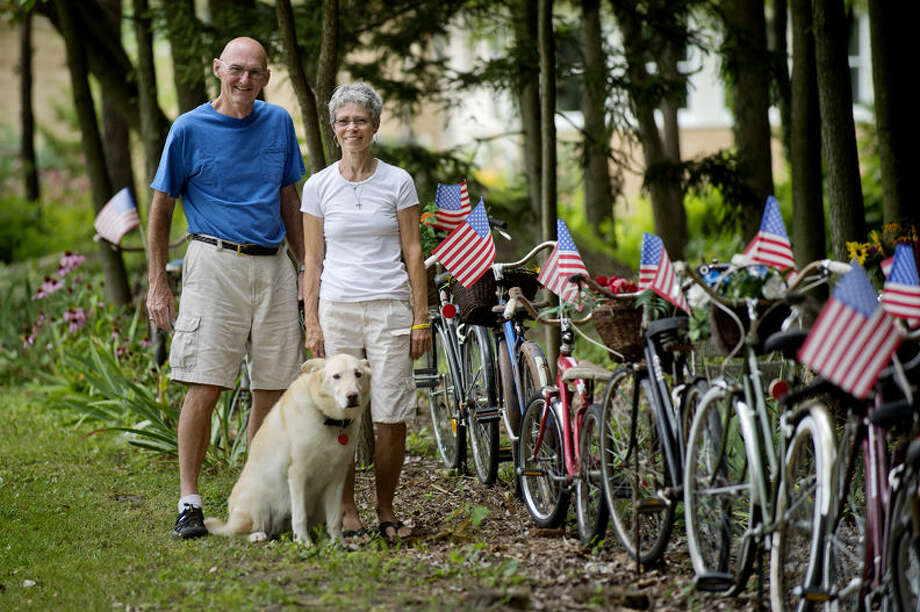 """Sherryand Larry Jacobs pose with their dog Nya in front of their """"bicycle fence"""" on their property in Midland. Photo: Nick King/Midland  Daily News"""
