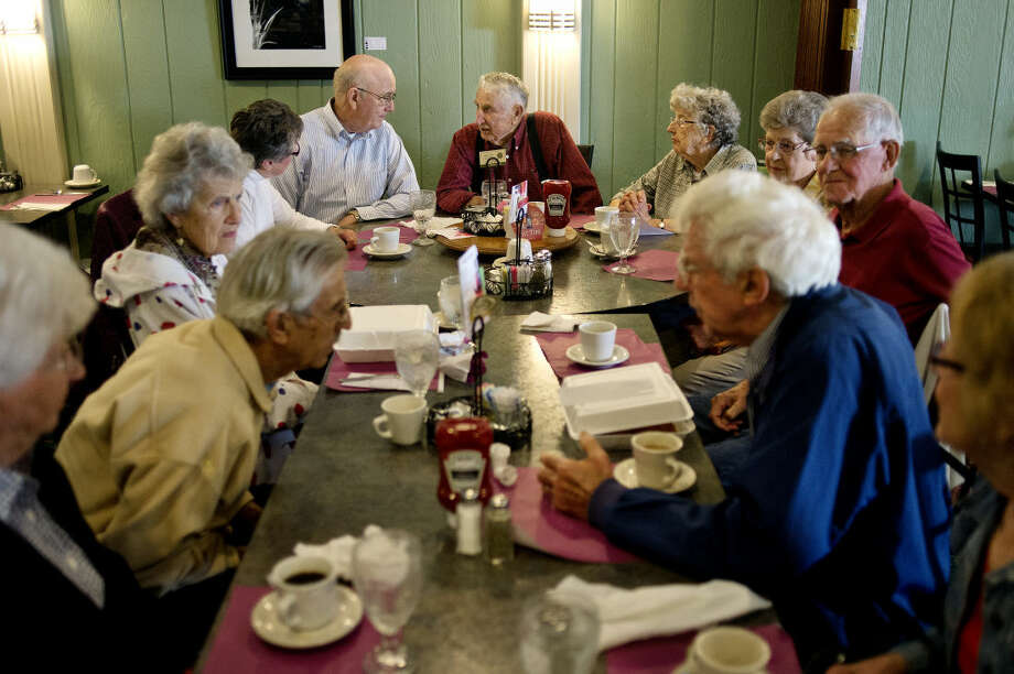 Claire Arnold, center, sits at the end of the table and talks with Jerry Nightlinger, left, during breakfast on Monday at Shirlene's Cuisine in Midland. Arnold's wife, Linda, sits to the right and Nightlinger's wife, Linda, sits to the left. Thirteen Arthur cousins have been enjoying breakfast together the second Monday of each month for the last 26 years. Photo: NICK KING | Nking@mdn.net