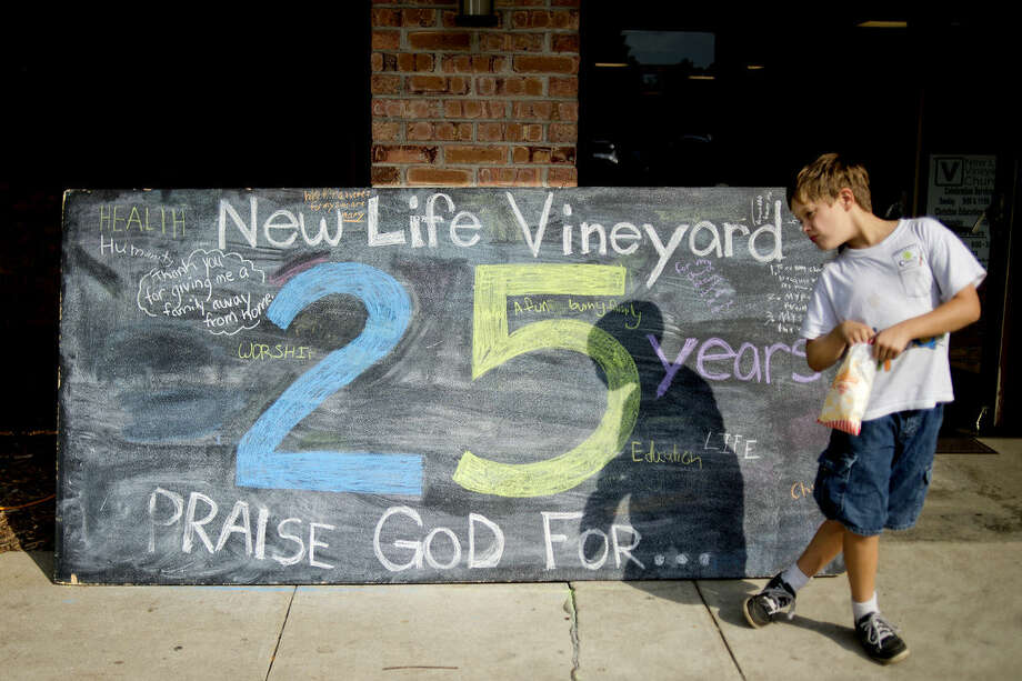 Matthias Francisco, 9, eats popcorn in front of chalk board with messages relating to the 25 years of the church on Saturday during a neighborhood party and 25th anniversary celebration at New Life Vineyard Church in Midland. The free event, which was open to all, featured carnival games, food and live music. Photo: Nick King/Midland  Daily News