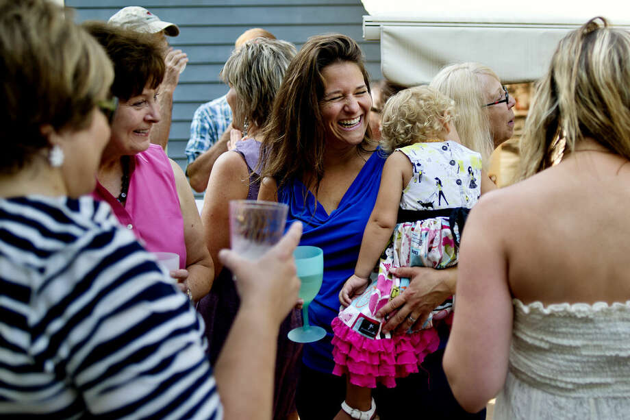 Karen Gondek, center, holds her daughter, Dylan, while talking with guests at a recent neighborhood party at her Midland home. Photo: NICK KING | Nking@mdn.net