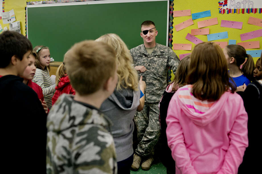 Staff Sgt. Eric Petersen answers questions at Plymouth Elementary last week. Petersen, a former U.S. Marine and current U.S. Army airborne serviceman, fielded questions about his military life ranging from what soldiers eat to his combat experience in Afghanistan. Photo: NEIL BLAKE | Nblake@mdn.net