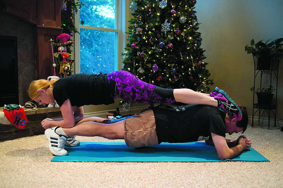 Matt Rassette and his wife Kathy demonstrate a planking photo in their home that they took during Planks-giving, a fitness challenge that they did before Thanksgiving. Matt is now leading the 21 Day Fit-Mas Challenge to encourage friends to stay active during the holidays. Photo: Neil Blake/Midland Daily News