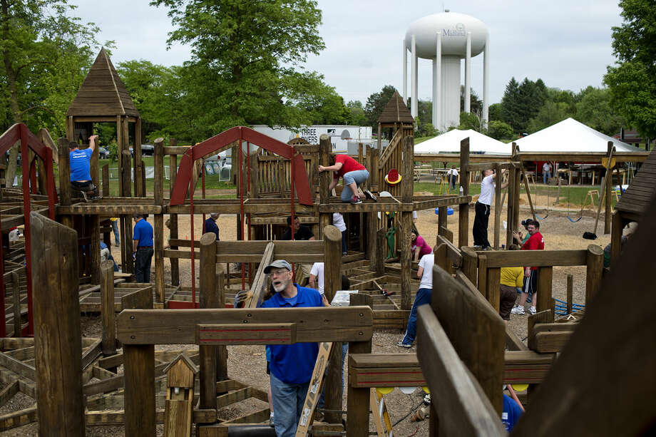 Midland Kiwanis member Earl Soules, center, sands the wood at the FunZone playground while volunteering at Plymouth Park in June. The playground was remodeled with new play equipment, a new picket fence and more. Photo: Nick King | Midland  Daily News