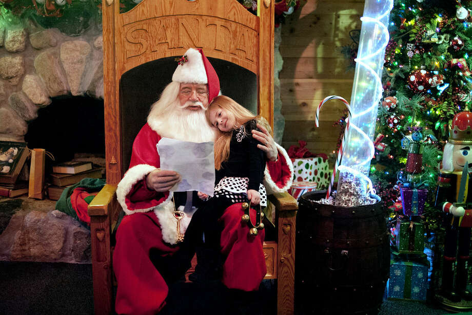 "Ella Batcke, 4, of Baldwin, rests her head on Santa as he looks over her Christmas list at the Santa House on Sunday in Midland. Ella came to the Santa House to visit with Santa and to carry a sign protesting the Huffington Post's recently published ""Naughtiest Girls"" list, which named 'Ella' as number one. Ella's grandmother, Pam Nash, of Midland, made the protest sign. Photo: Nick King/Midland  Daily News"