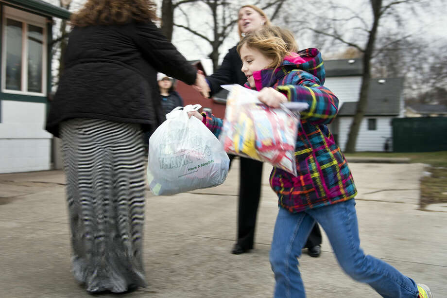 """Addie McLaughlin, 7, runs into the Open Door Crisis Shelters and Soup Kitchen, carrying bags of donations. Instead of presents for herself for her Dec. 4 birthday,Addie told her parents she wanted to give presents to those who are less fortunate. The project, dubbed """"Addie's Gift,"""" collected two vehicles full of donated food and clothing, as well as $1,212 to be presented to Open Door. Photo: DANIELLE McGREW 