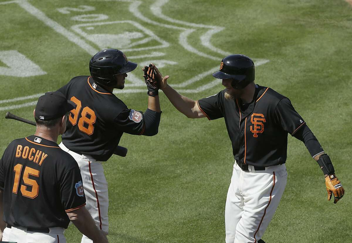 San Francisco Giants' Hunter Pence, right, celebrates with Miguel Olivo (98) and manager Bruce Bochy (15) after hitting a home run against the Oakland Athletics during the fourth inning of a spring training baseball game in Scottsdale, Ariz., Monday, March 21, 2016. (AP Photo/Jeff Chiu)