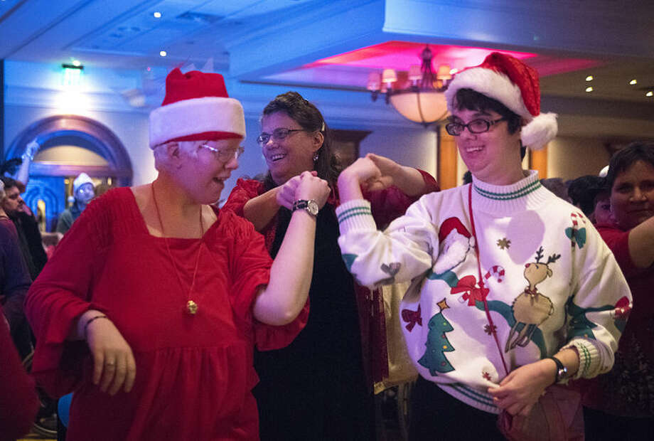 Barb McGee twirls Megan Moreno, left, and Mindy McGee at the annual holiday dance hosted by People First of Midland, which is part of The Arc of Midland, on Thursday at the Great Hall. Photo: Danielle McGrew/Midland Daily News