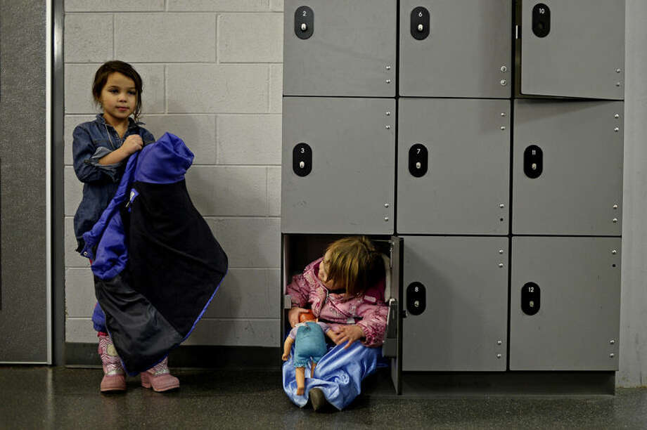 Mia Jaime, 6, left, picks up her coat as her sister Sophia, 2, sits in a small locker Wednesday night at the Midland Civic Arena. The siblings were waiting for the brothers Pee Wee hockey game to finish. Photo: Sean Proctor/Midland Daily News