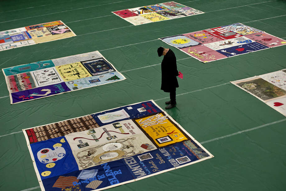 "Leo Romo, of Saginaw, looks at panels of the National AIDS Quilt which was on display on Monday at Delta College's Pioneer Gymnasium. Romo said that he came to see the quilts to ""honor people who died from AIDS."" Photo: NICK KING 