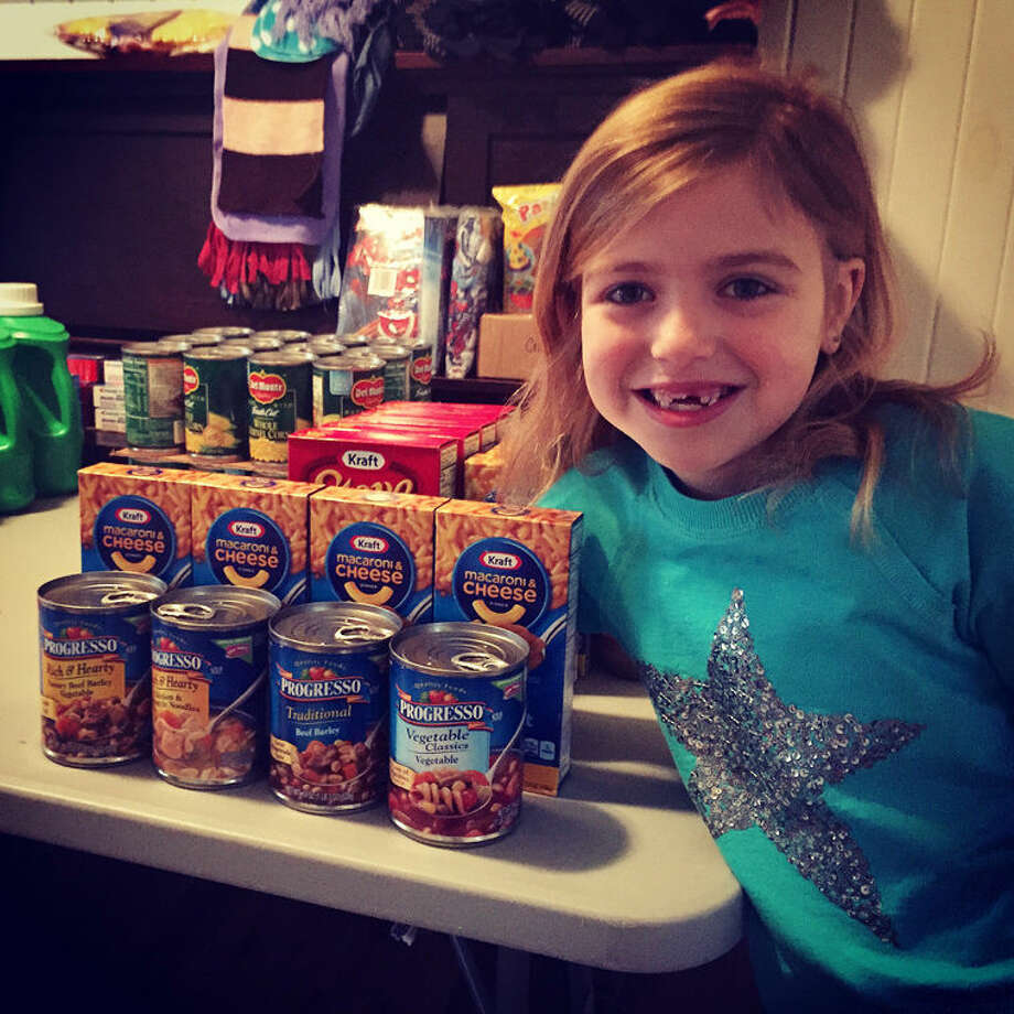 Addie McLaughlin, 7, poses for a photo next to some of the donations she has received that will be given to Shelterhouse and Midland's Open Door. Photo: Rachel McLaughlin | Photo Provided