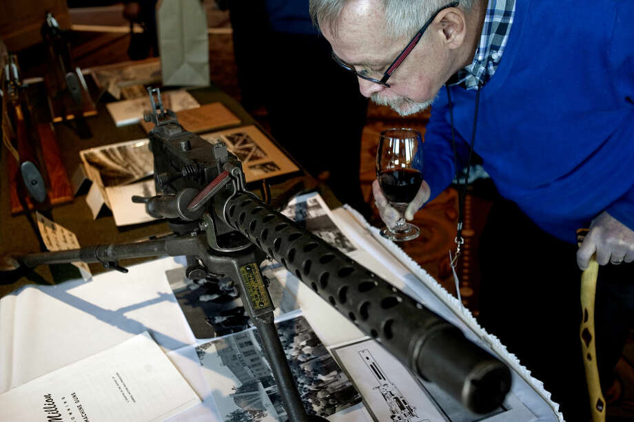 Former employee Terry Sutter looks at a machine gun which was built in Plant 2 from 1942-1945. Sutter was attending the General Motors Saginaw Steering Gear Plant 2 reunion on Monday at Apple Mountain Resort's Grand Ballroom. Photo: NICK KING | Nking@mdn.net