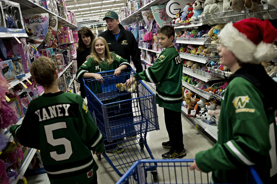 Allyson Hundley, 10, center, and teammates on her 2004 Midland Northstars travel hockey team explore the toy aisles of Meijer on Tuesday evening. Photo: SEAN PROCTOR | Sproctor@mdn.net