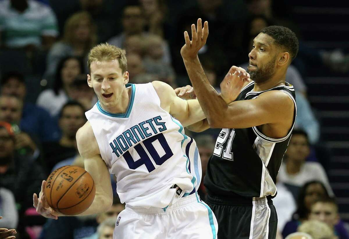 CHARLOTTE, NC - MARCH 21: Cody Zeller #40 of the Charlotte Hornets and Tim Duncan #21 of the San Antonio Spurs battle for a loose ball during their game at Time Warner Cable Arena on March 21, 2016 in Charlotte, North Carolina.NOTE TO USER: User expressly acknowledges and agrees that, by downloading and or using this photograph, User is consenting to the terms and conditions of the Getty Images License Agreement.