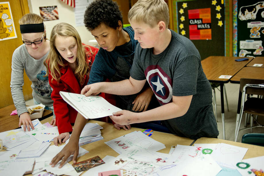 From left, Northeast Middle School seventh-graders Grace LaBoute, Ella Torsin, Xander Brooks and Alex Ernst go through the pile of cards made and collected at the school over the past week to send to Addie Fausett, a 6-year-old Utah girl who is dying from an undiagnosed illness causing cerebral atrophy. Alex, who spearheaded the project, has been working on it during his lunch period. Photo: NICK KING | Nking@mdn.net