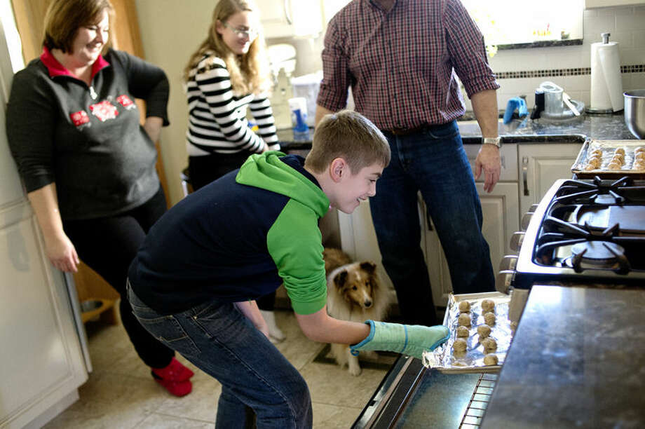 Blake Ferruzzi, center, 11, takes snowball cookies out of the oven as, from left, his mother Shari, sister Cara, 15, and father Art look on at their Midland home. The family makes Christmas cookies together each year and Shari participates in a cookie exchange. Photo: Nick King/Midland  Daily News
