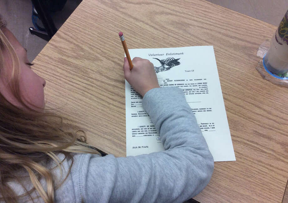 A Siebert Elementary School student signs an enlistment form during a lesson on life as members of the Michigan Infantry during the American Civil War. Photo: Photo Provided