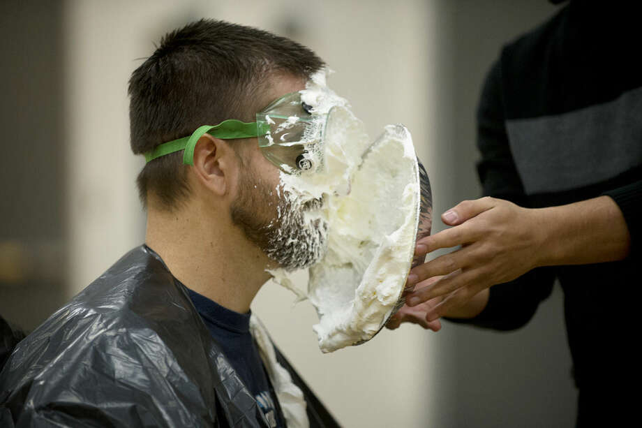 Meridian football coach Mike Bilina takes a pie in the face from one of his players, Luis Korpal, on Thursday during a fundraiser that Meridian students held to raise money to adopt local families for Christmas. Photo: Neil Blake/Midland Daily News