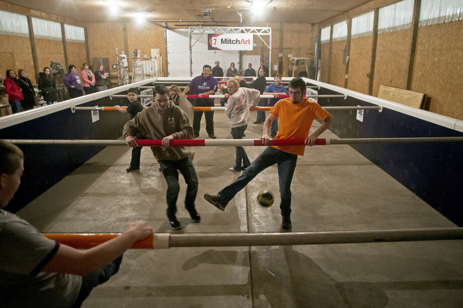 "Matt Schatten, left, and Curtis Weitfeldt, right, play ""human foosball"" in the pole barn behind ABC on 7730 W. Wackerly. Photo: SEAN PROCTOR 