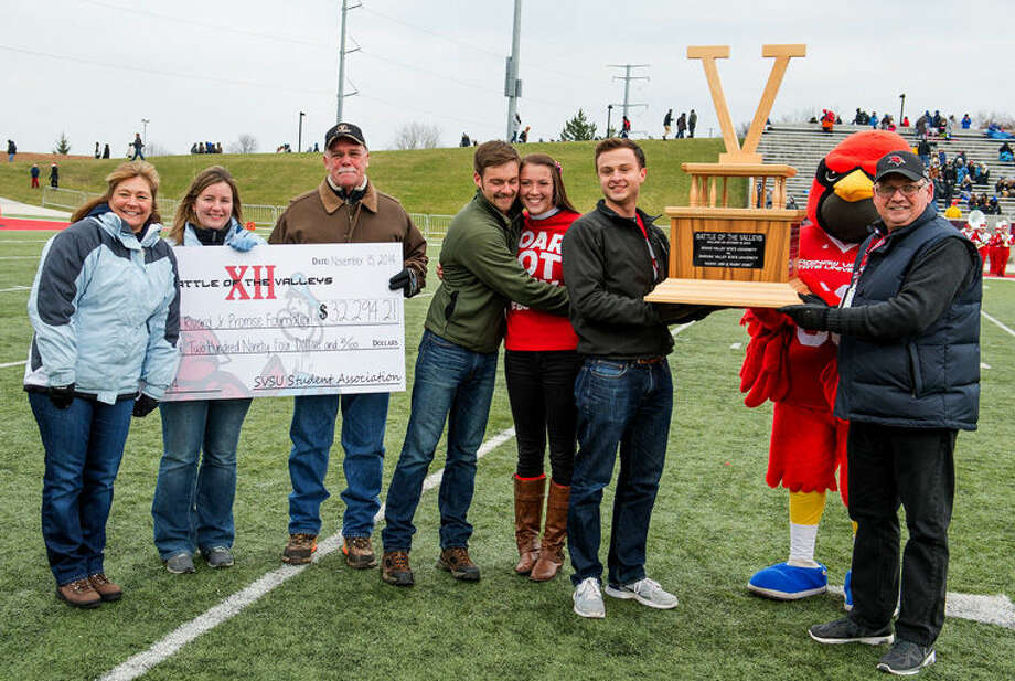 "SVSU President Donald Bachand, far right, and SVSU Student Association President Joey Rexford hold the ""Victoria"" trophy awarded annually to the school that wins the Battle of the Valleys fundraising competition. Emily VanFleteren (third from right), SVSU's Battle of the Valleys chair, is embraced by Josh Rivard, a 2014 SVSU graduate and younger brother of the late Cory Rivard, as members of the Rivard family hold the check for $32,294. Photo: Mike Randolph 