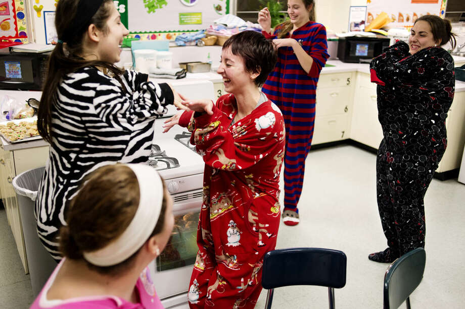 From left, Lauren Siegmund, 15, Olivia Beasley, 15, Alli Dotson, 14, and Emily Dean, 16, goof off in their onesies during a cookie making party at Northeast Middle School on Friday. Photo: NEIL BLAKE | Nblake@mdn.net
