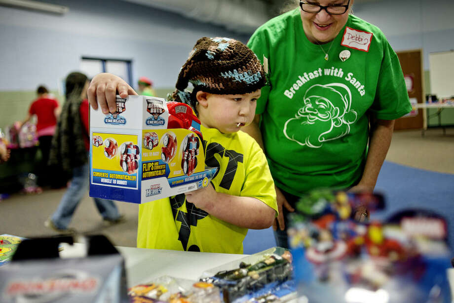 Davis Gaes, 6, picks out a toy with the help of volunteer Debbi Sandow during the Jayden Lamb Toy Store/Breakfast with Santa event at Messiah Lutheran Church. Children were given the opportunity to pick out a toy in a room filled with both boy and girl-related gifts. The Jayden Lamb Memorial Foundation and Filling Midland's Cup partnered to put on the event. Photo: NICK KING   Nking@mdn.net