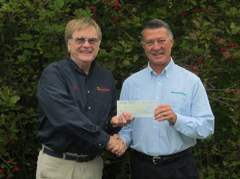 Tom Begin, right, East Regional manager, Public Affairs, Consumers Energy, presents the check to CNC Executive Director Dick Touvell.