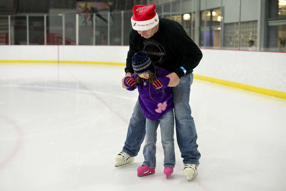 Jon Dennis of Texas helps his daughter Rosemary, 6, skate at the Midland Civic Arena on Friday. They were in Midland visiting family over the holidays. The arena has skating open to the public daily over winter break. Photo: Neil Blake/Midland Daily News