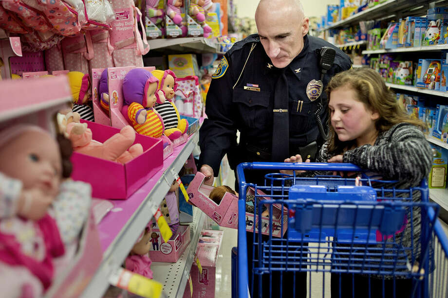 Midland Police Chief Cliff Block, left, helps McKenna Herkel, 7, pick out a doll for her cousin during the Shop with a Hero event on Monday at the Midland Meijer. Herkel picked out items for family members as well as for herself. The event, a partnership involving Meijer, the Salvation Army and local emergency personnel, teams up underprivileged children with a heroes to shop with $100 gift cards. Photo: Nick King/Midland  Daily News