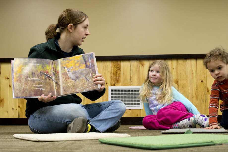 """Chippewa Nature Center educator Victoria Zablocki reads """"First Snow in the Woods"""" to Ava Petroski, 4, and Kayan Ciolino, 2, at the center. During the free activity, children ages 3 to 5 spend an hour learning about nature and sometimes venturing outdoors Photo: NEIL BLAKE 