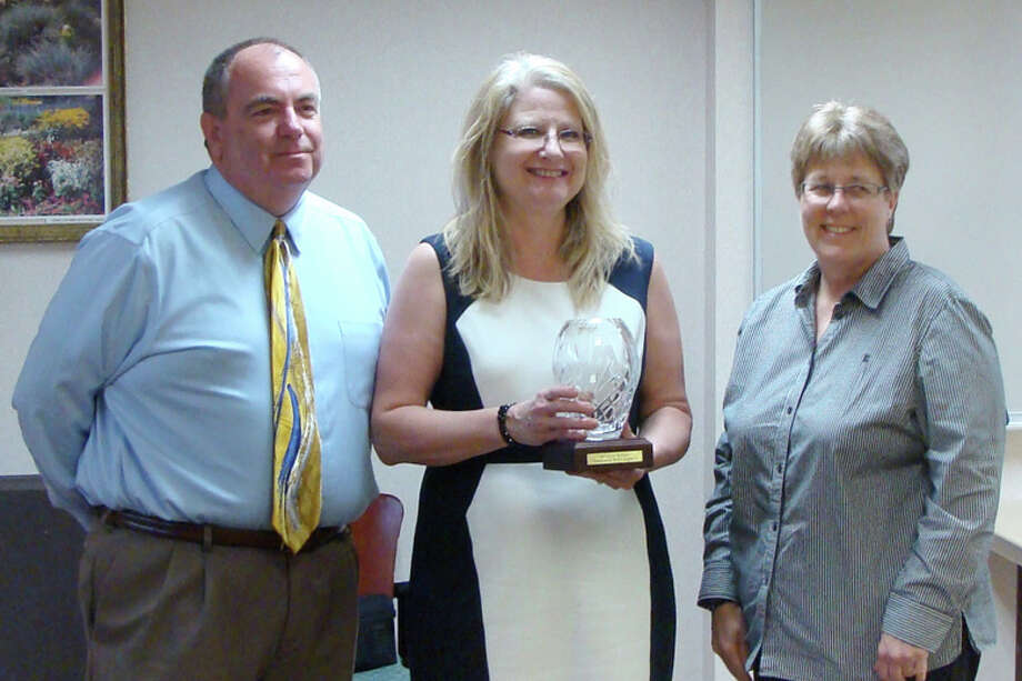 Bev Wenzel, center, is shown receiving the 2014 Region 4 Champion for Children award from Charles Schwedler and Mary Pitchford.