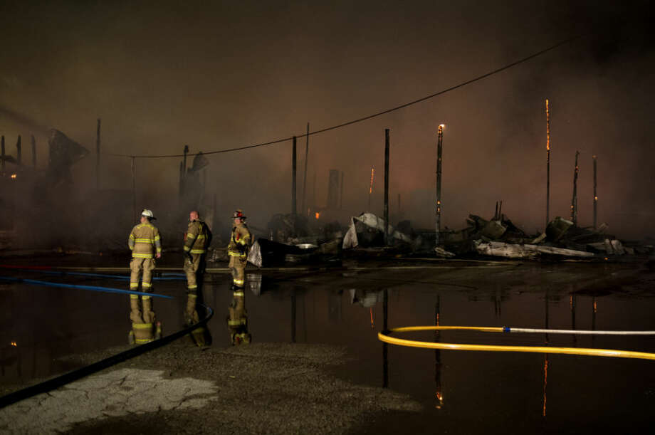 Kawkawlin Township Fire Department firefighters stand near the skeletal remains of a building at the King Lumber Company off of Fraser Road in Bay City late on Saturday. The fire, which consumed a large section of the lumber yard, started on Saturday night and continued into Sunday morning as firefighters from multiple fire departments battled the fire. Photo: Neil Blake/Midland Daily News
