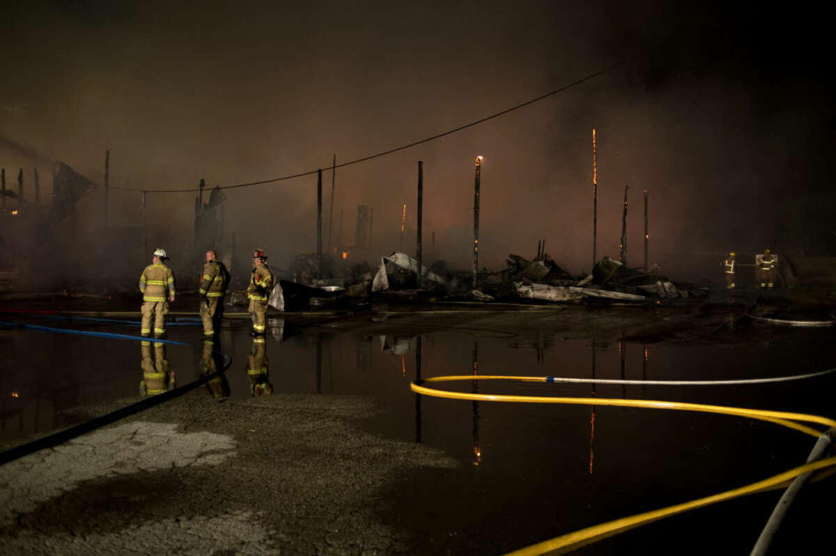 Kawkawlin Township Fire Department firefighters stand near the skeletal remains of a building at the King Lumber Company off of Fraser Road in Bay City late on Saturday. The fire, which consumed a large section of the lumber yard, started on Saturday night and continued into Sunday morning as firefighters from multiple fire departments battled the fire.