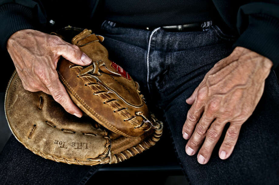 "Gary Rocha, of Saginaw, holds his glove in his hand Monday evening as he watches the Great Lakes Loons play the Lake County Captains at Dow Diamond. Rocha, an art teacher at Nouvel Catholic Central High School and Saginaw Valley State University, has been attending Loons games since 2007 and usually tries to come once a week, always sitting in section 104. Rocha plays vintage baseball with the Mighty River Hogs said he is used to catching balls with his bare hands, but brings his glove because of the speed of potential foul balls hit into the bleachers from left-handed hitters. He said the balls the Mighty Rivers Hogs use are also hand wound, making them somewhat softer than the machine wound balls used during Loons games. ""They're harder than bricks,"" he said. Photo: Sean Proctor"