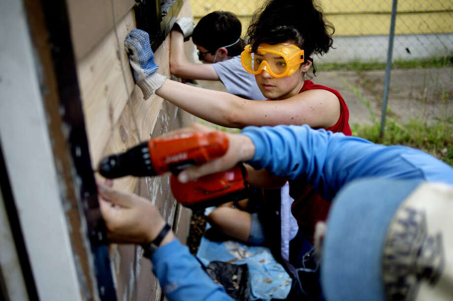 """Kelly Fin, 18, of Midland, holds a board in place as Jerry Klosowski, bottom, screws it in to place as they work on the siding of a home off Harold Street during the One Week, One Street neighborhood revitalization project in Saginaw last week. Fin said that she volunteered """"to make a difference in the Saginaw community an to be a part of something bigger than myself."""" Volunteers worked to improve the homes of residents over the course of the week. Photo: NICK KING 