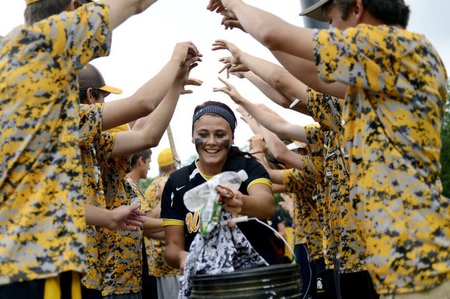 Bay City Western's Kaylynn Carpenter, center, leaves the field through a spirit tunnel made up of Warriors student fans Thursday at Secchia Stadium. Bay City Western beat Romeo 2-1 in the Division 1 state semifinal game. Photo: NICK KING | Nking@mdn.net