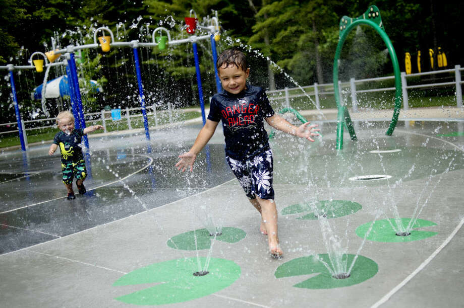 Thomas Peistrack, right, 4, and his brother, Samuel, 2, both of Standish, play in the spray park at Sanford Lake Park. Photo: NICK KING | Nking@mdn.net