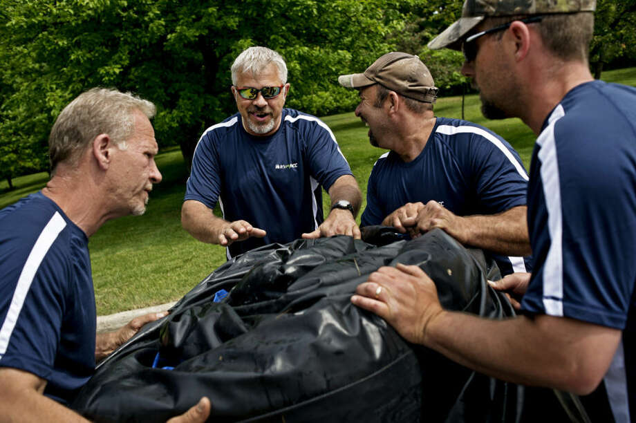 From left; Doug Green, Joe Calleja, Director of Facilities at Greater Midland Community Centers, Mike Heilig and John Oliver work on unloading and inflating a bounce house in the Grace A. Dow Library parking lot Friday morning. The bounce house will be part of the Summer Art Fair that runs Saturday and Sunday from 10-5 on the grounds of the Midland Center For the Arts and spilling into the surrounding area including St. Andrews Street and the library parking lot. The fair will feature over 100 artist booths along with food vendors, street musicians, artist demonstrations and a children's activity corner. Photo: Sean Proctor