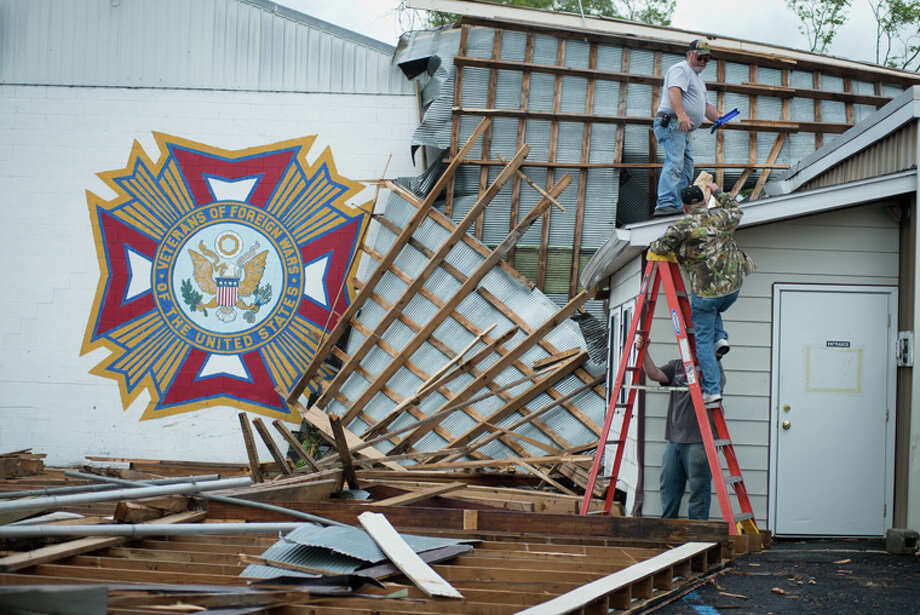 Greg Green and Ron Green, on ladder, climb up to survey the damage caused by a tornado at the VFW Post 7435 Tuesday in Hale. Several buildings and trees sustained damage from the storm. Photo: AP Photo | The Bay City Times, Yfat Yossifor / The Bay City Times